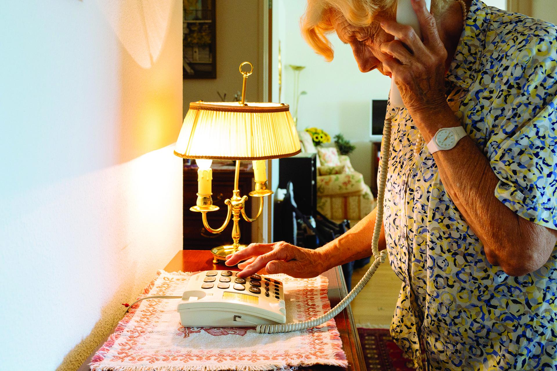 Photo: Une personne malvoyante âgée compose un numéro sur son téléphone à touches agrandies et contrastées.