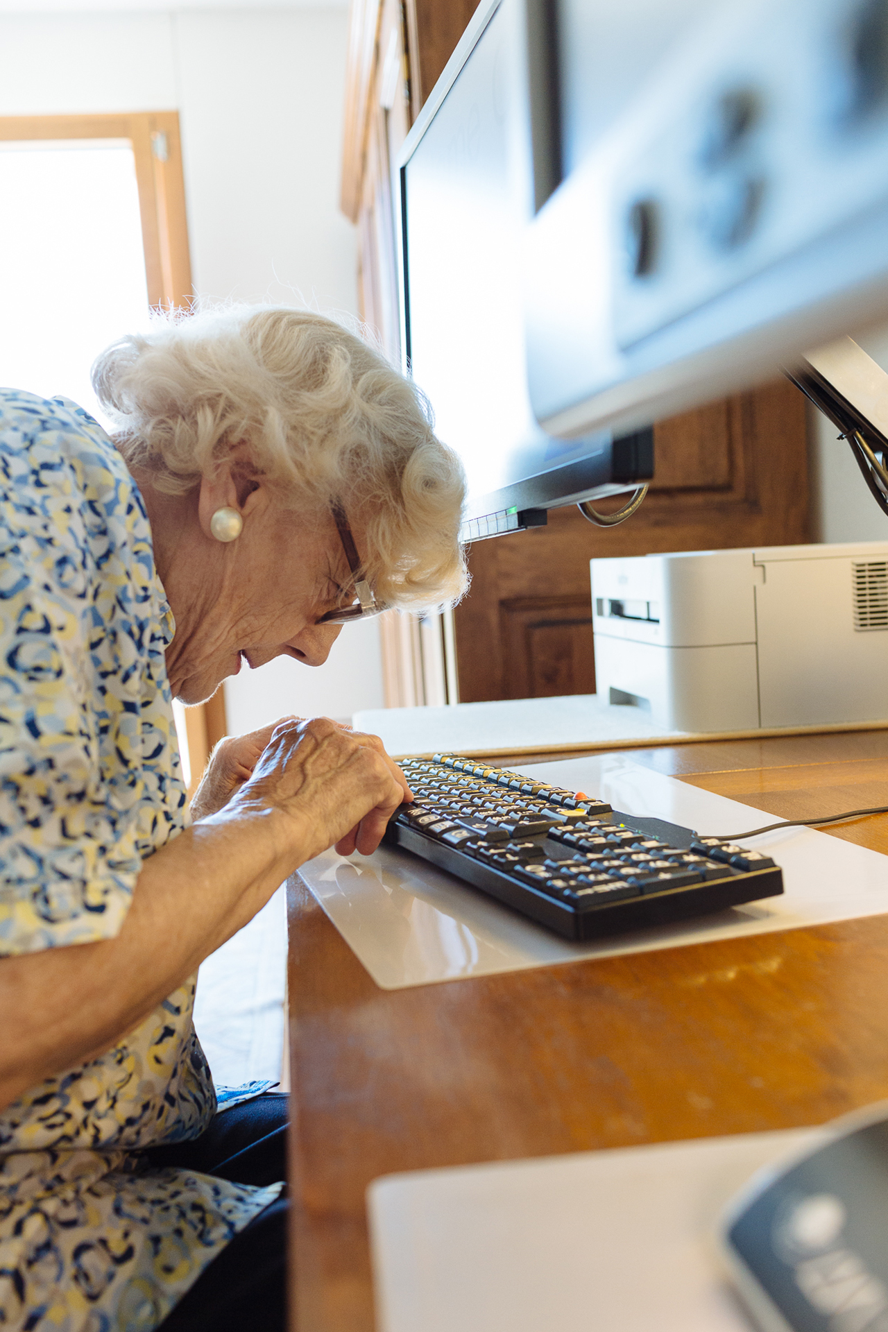 Photo: Une personne malvoyante âgée utilisant un clavier informatique.