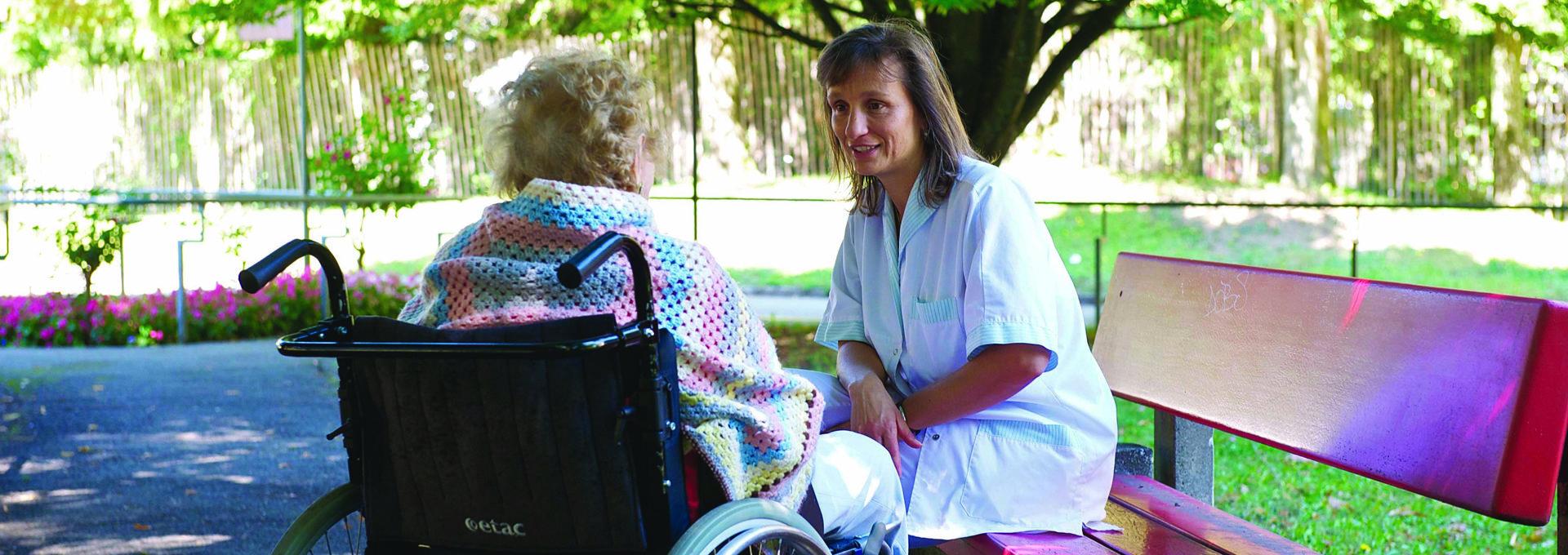 Photo: Conversation entre une résidente en fauteuil roulant et une soignante.