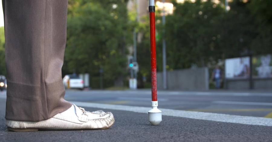 Photo: Une canne longue posée au sol devant les pieds: cette personne attend le bus.