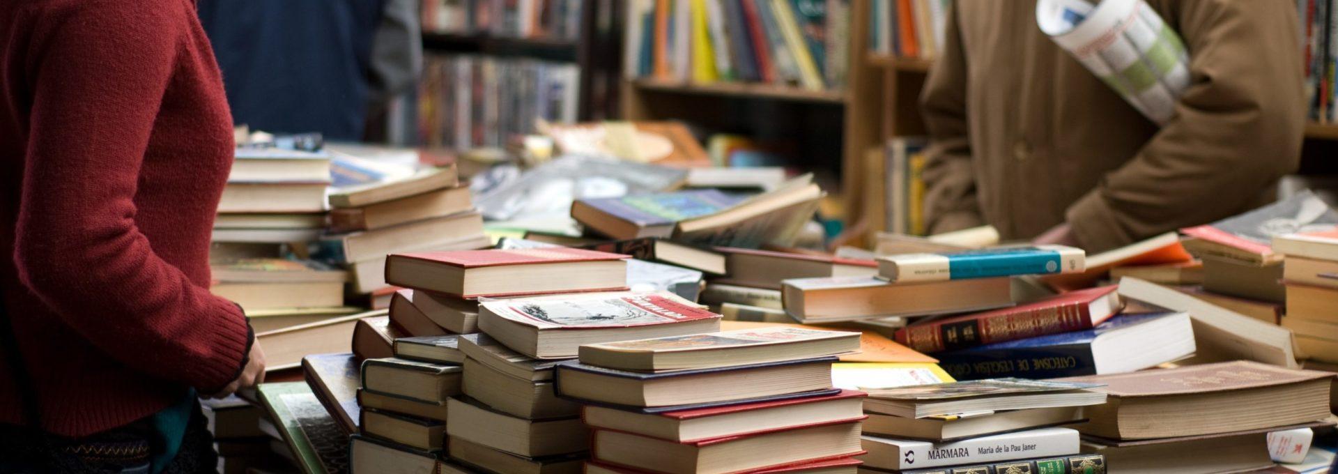 Photo: Deux personnes chinent des piles de livres posés sur une table dans une bibliothèque.