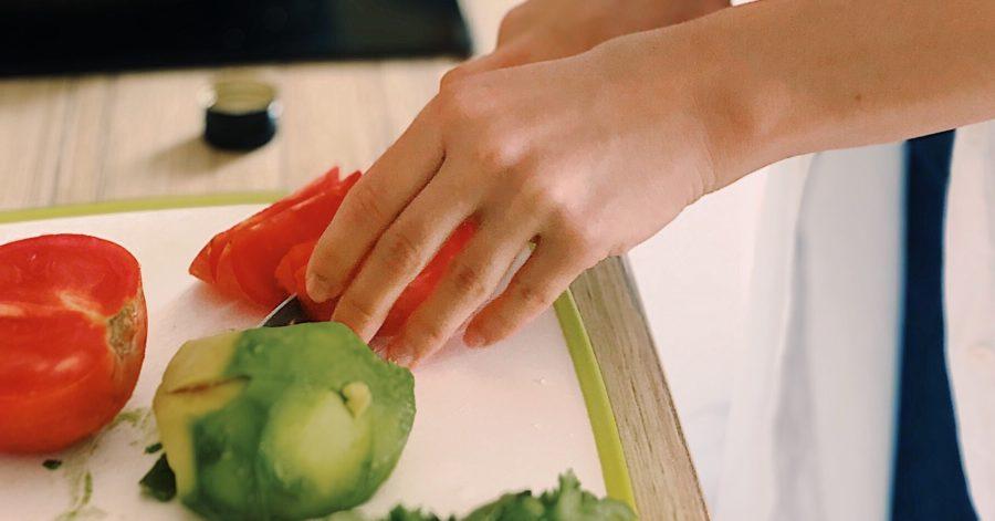 Photo: Gros plan sur des mains coupant une tomate sur une planche à découper.
