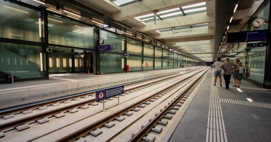 Photo: Vue intérieure d'une gare CEVA. Les voies sont à gauche et le quai, situé sur la droite, est muni de lignes de sécurité et de champs d'éveil.
