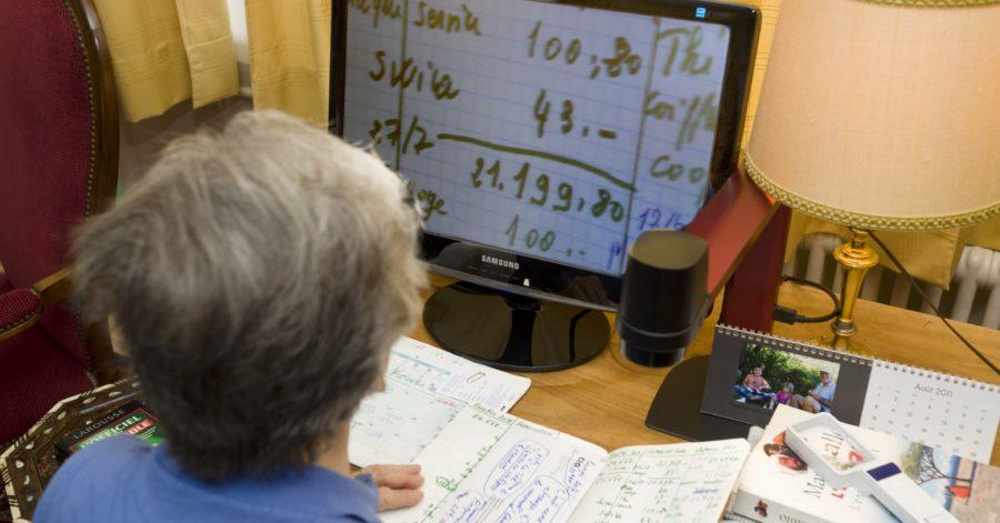 Photo: Une personne lit sa comptabilité personnelle avec un téléagrandisseur.