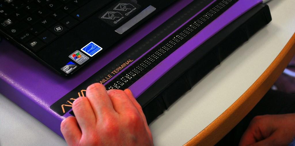 Photo: Une main lit sur une ligne braille informatique.