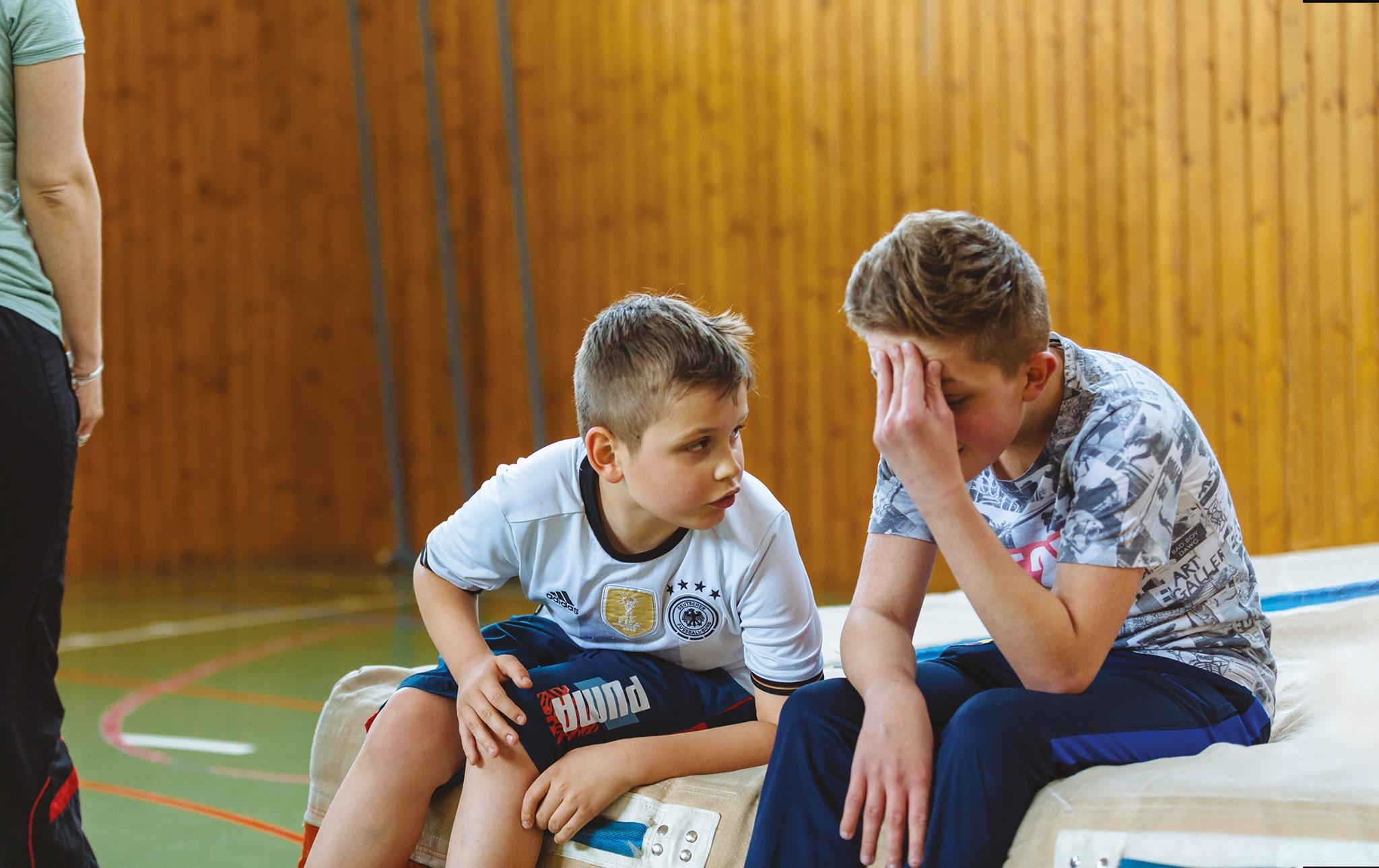 Photo: Deux enfants malvoyants se reposent sur un gros tapis de gym et discutent.