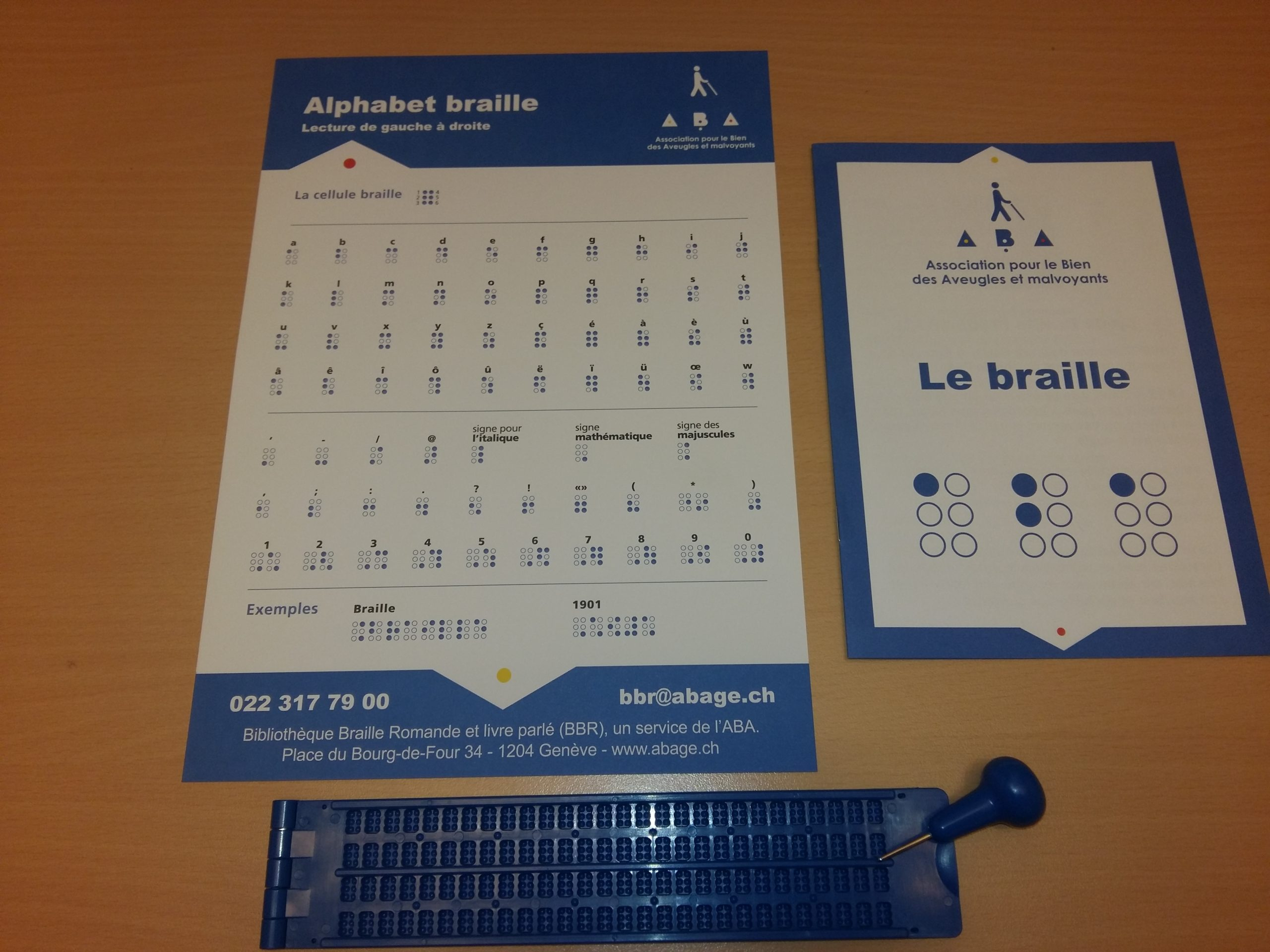 Photo: Matériel utilisé lors de sensibilisation au braille: un alphabet braille, un livret explicatif et une réglette braille avec son poinçon.