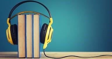 Photo: Un casque audio est posé sur trois livres debout, comme s'il écoutait leur contenu.