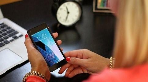 Photo: Illustration du télétravail, on y voit deux mains utiliser un Smartphone devant un ordinateur.