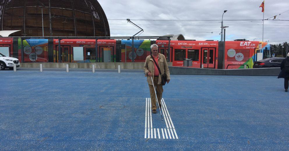 Photo: Jean-Marc Meyrat se déplaçant avec sa canne blanche sur des lignes de guidage vers le CERN à Genève.