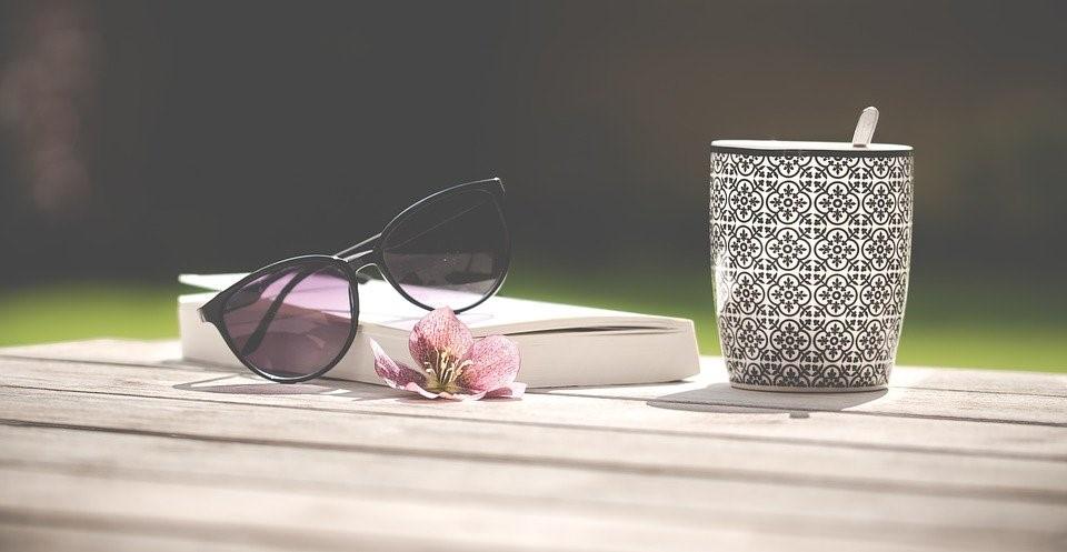 Photo: des lunettes de soleil sont posées sur un livre fermé posé sur une table, à côté d'un mug.