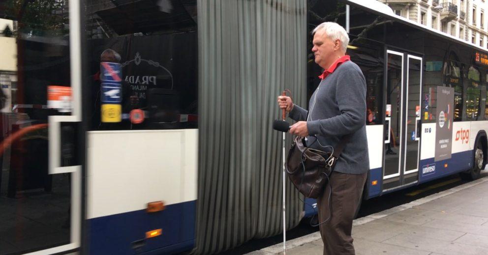 Photo: Jean-Marc Meyrat debout devant un bus TPG avec sa canne blanche.