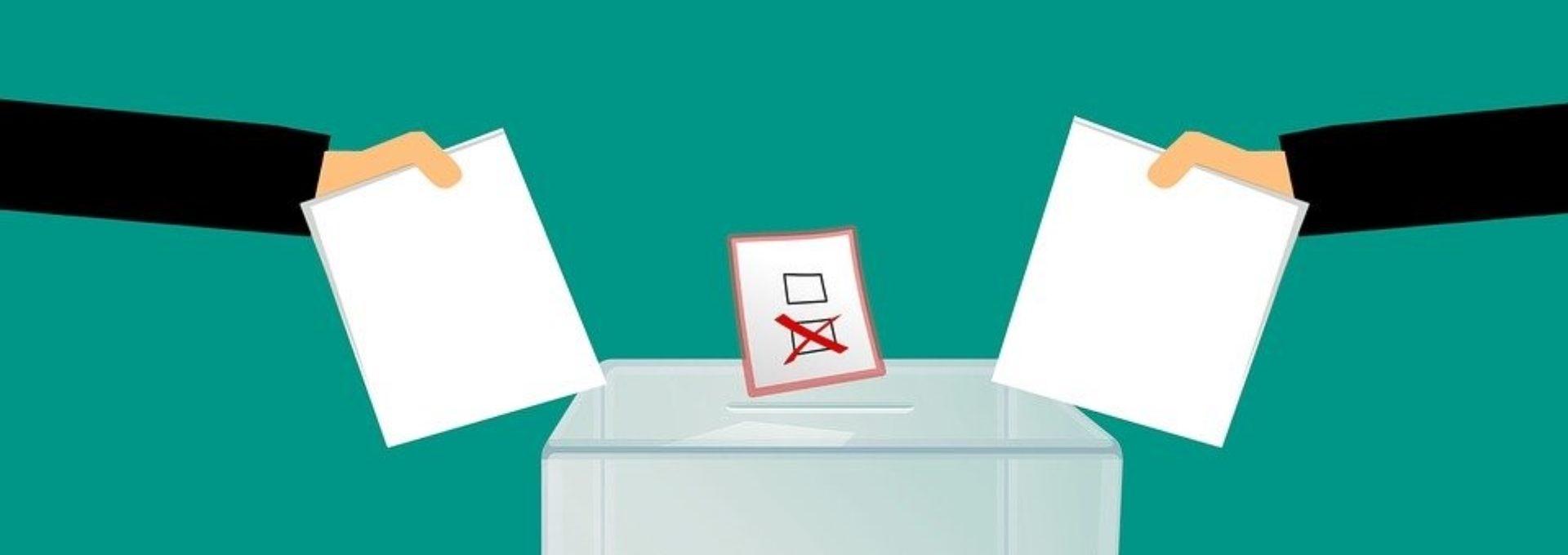 photo: Deux bulletins de vote se font déposer dans une urne.