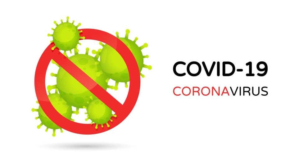Photo: panneau d'interdiction rempli de virus dessinés avec la mention COVID-19, corona virus à sa droite