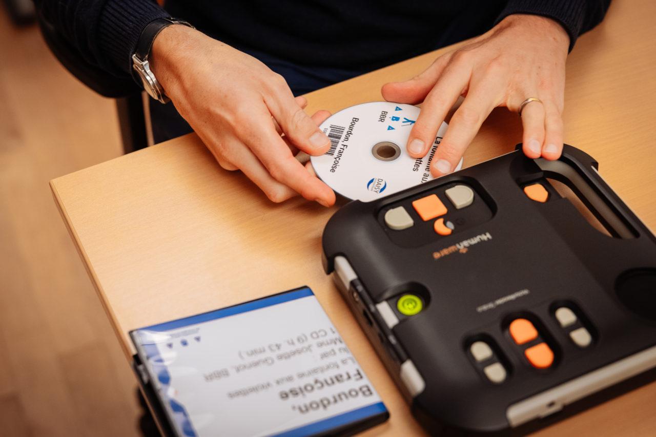 Photo: introduction d'un CD dans un appareil de lecture audio.