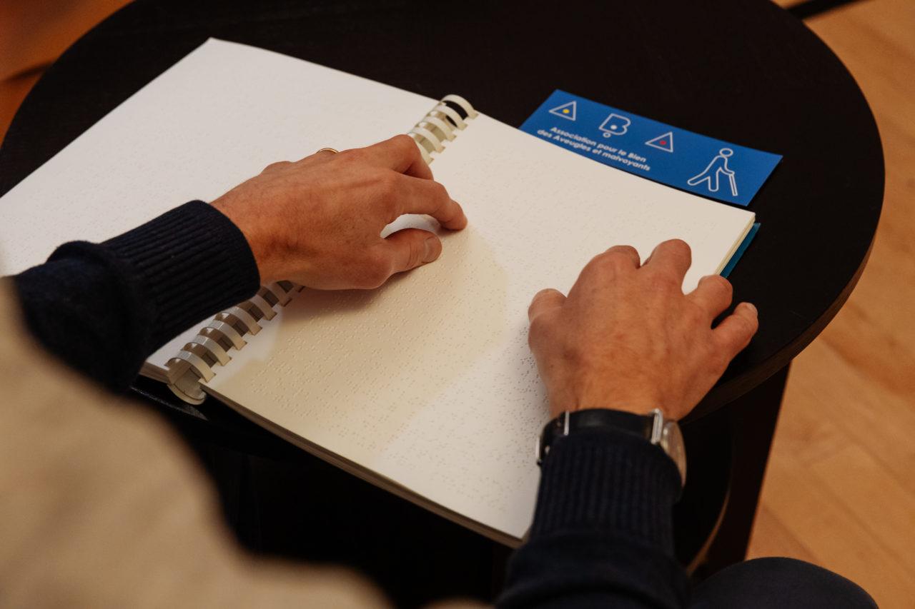 Photo: deux mains parcourent un livre en braille ouvert