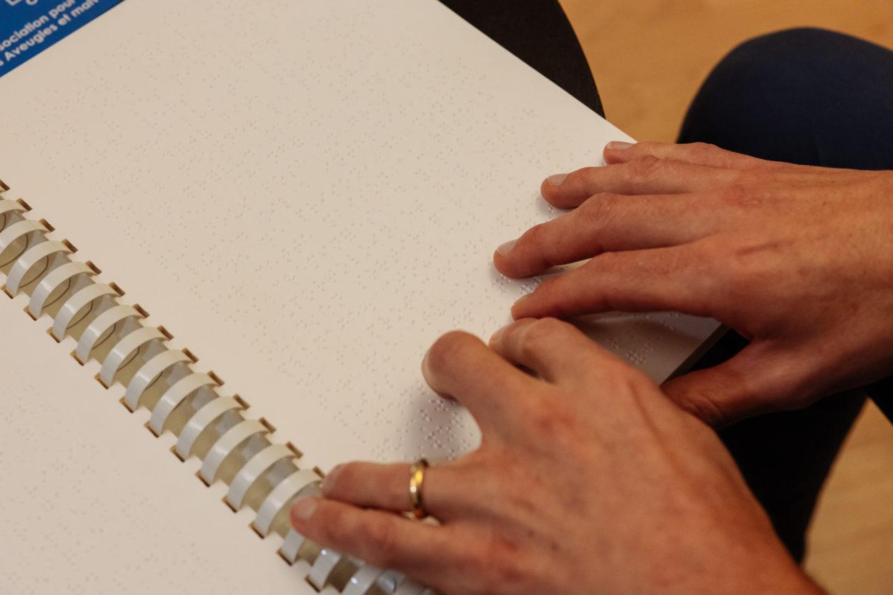 Photo: gros plan sur les deux mains lisant un texte en braille