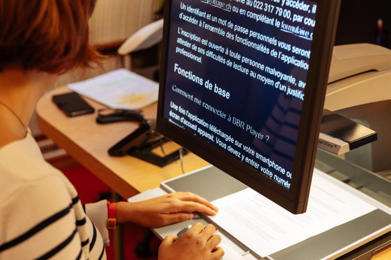 Photo: une personne malvoyante lit un document grâce à une télévision en circuit fermé.