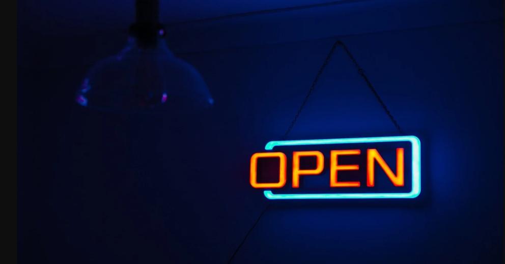 """Photo: une enseigne lumineuse orange """"open"""" sur fond bleu foncé."""