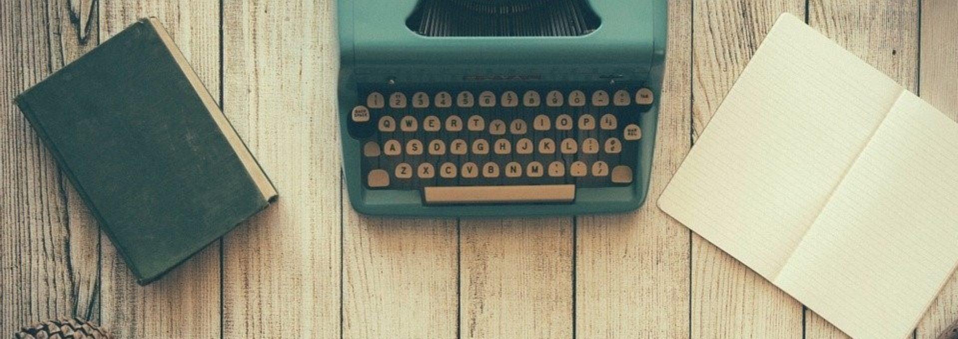 Photo: bureau sur lequel sont disposés une machine à écrire mécanique, une feuille de papier, des lunettes et un calepin.