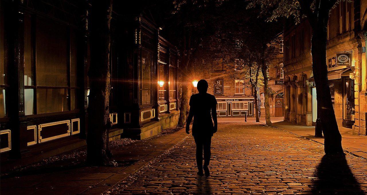 Photo: une personne marche dans une rue la nuit.