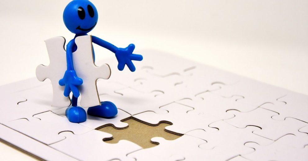 Photo: Bonhomme portant une pièce de puzzle pour compléter le plateau.
