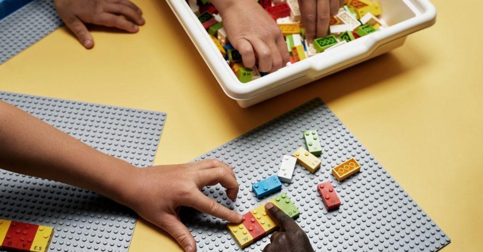 Photo: des mains d'enfants jouent avec les briques braille Lego.