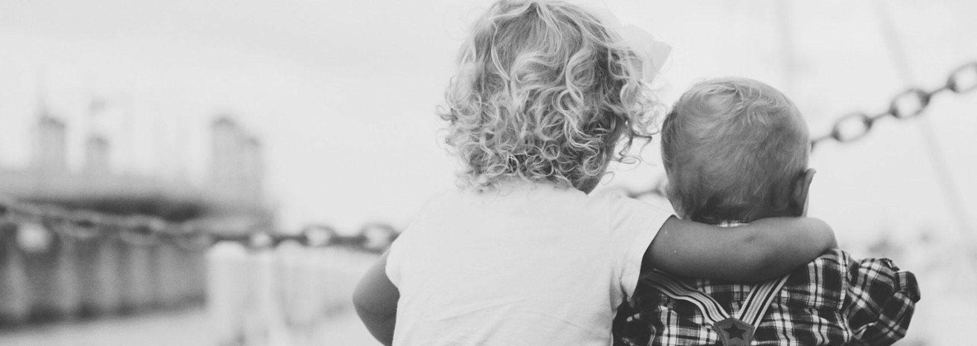 Photo: deux enfants assis se tenant par le cou.