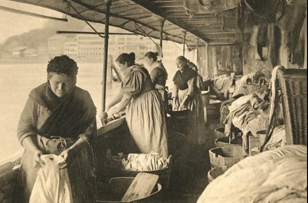 Des blanchisseuses nettoyant le linge au bord du Rhône sur des bateaux-lavoirs.